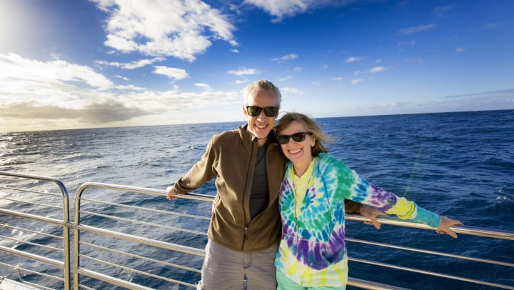 A senior man and woman leaning against the rails on a ship smiling with the ocean in the background.