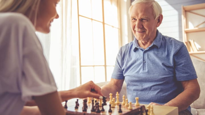 Young woman and older man are playing chess and smiling