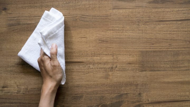 Close up of a hand holding a white cloth wiping a wood surface.