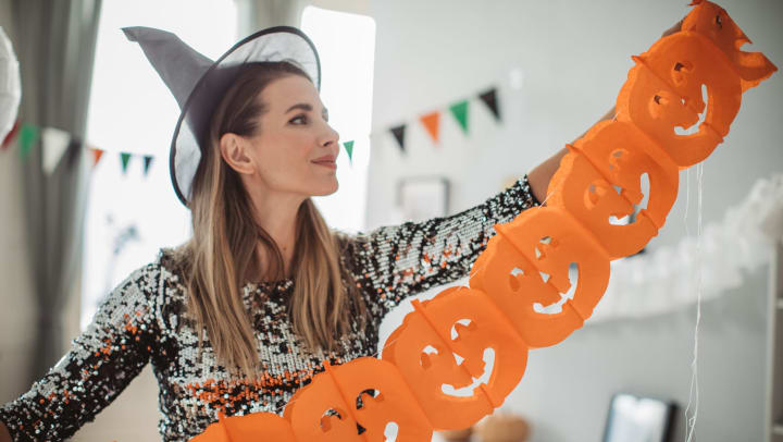 Woman hanging hand-made pumpkin decorations in her Cactus Forty-2 apartment