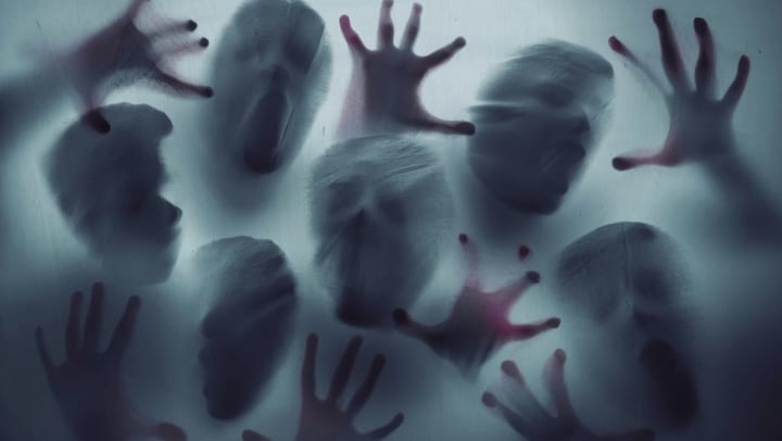 Scary ghost people reached out through a sheer sheet at a haunted house near Olympus Boulevard