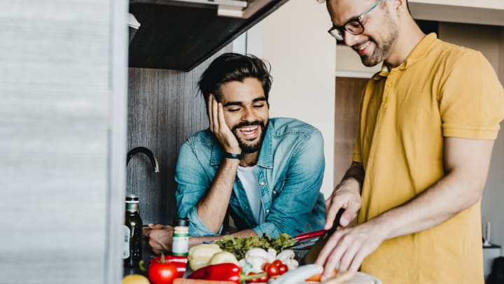 Couple in kitchen chopping vegetables together