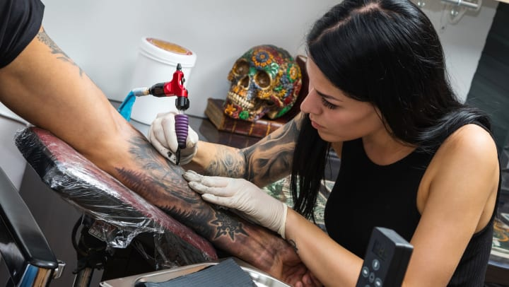 A tattoo artist adds a new design to a client's forearm.
