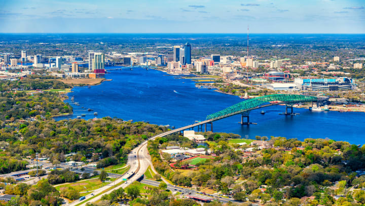 Aerial view of downtown Jacksonville with river, bridge, high-rise buildings, and trees on a sunny day