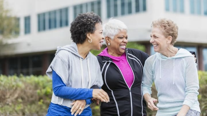 Three senior women wearing sweatshirts laughing and talking while they take a walk in the neighborhood near {{location_name}}.