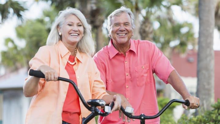 Two seniors outside sitting on bikes smiling