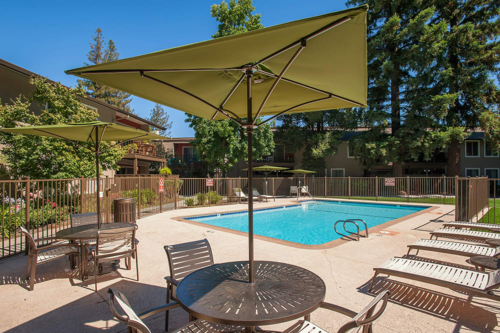 Table and chairs with an umbrella for a poolside lunch at Flora Condominium Rentals in Walnut Creek, California