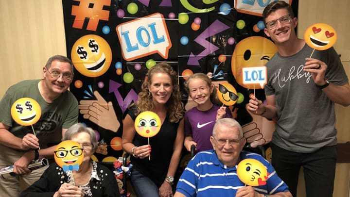Different generations pose holding emojis