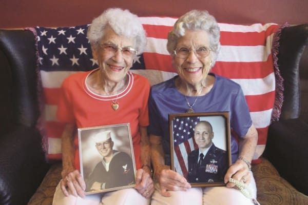 Two residents holding up photos at Estrella Estates Gracious Retirement Living in Goodyear, Arizona