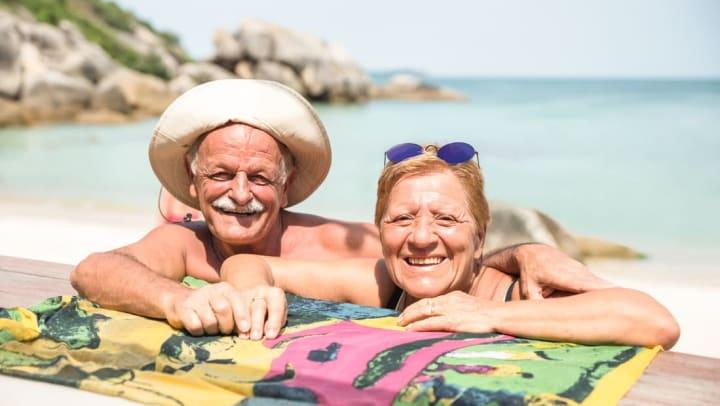 Two seniors sitting on the beach