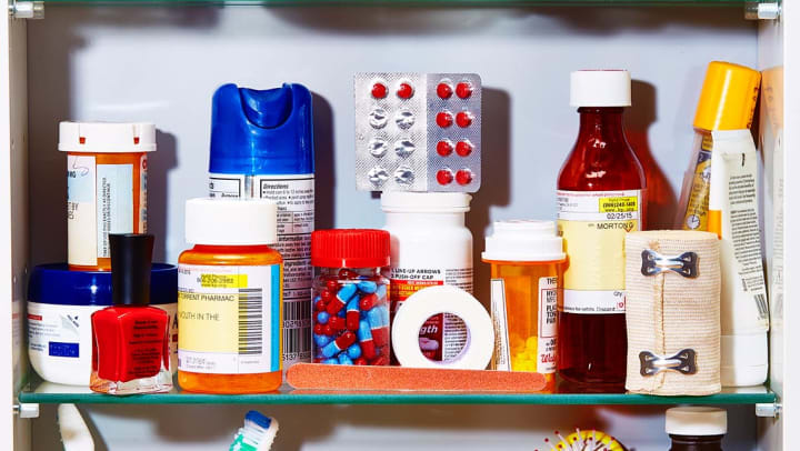 The inside of a medicine cabinet with several different types of prescription pills and first aid equipment.