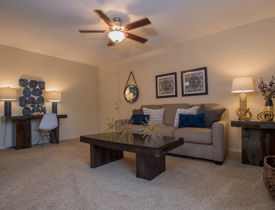 Living room with a ceiling fan at Woodscape Apartments in Oklahoma City, Oklahoma