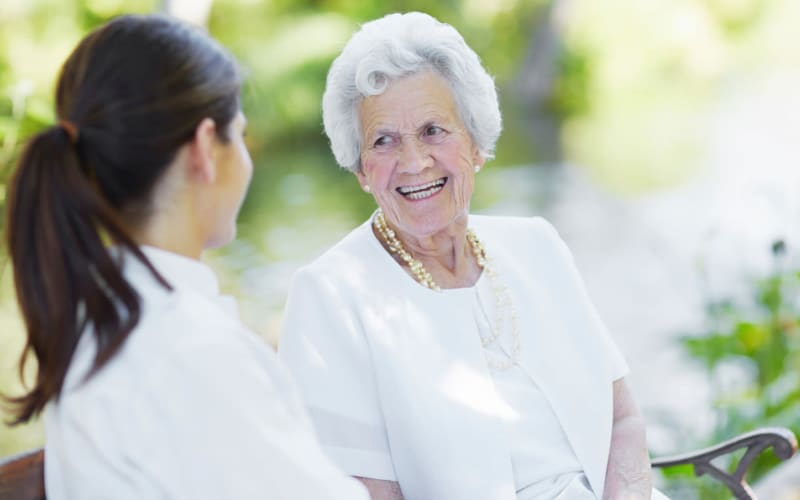 Senior living resident and staff member chatting at The Arbors at Dunsford Court in Sullivan, Missouri
