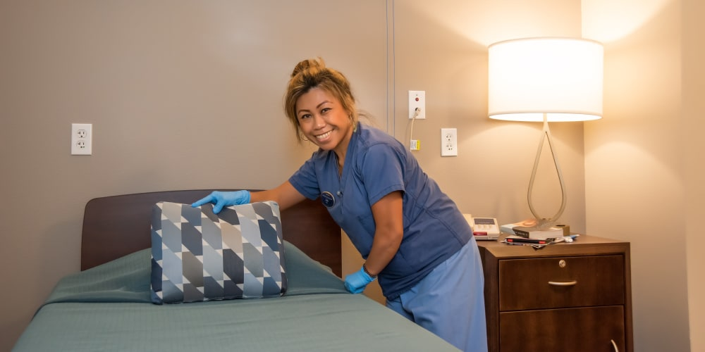 A woman staff member making the bed at Mission Healthcare at Bellevue in Bellevue, Washington.
