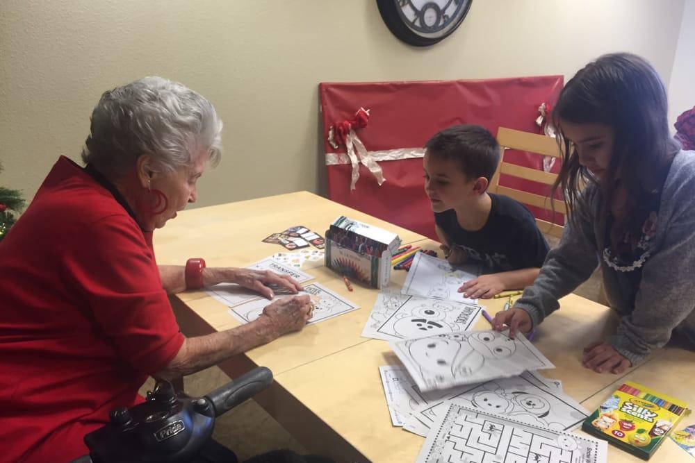 Senior resident enjoying coloring with grand kids