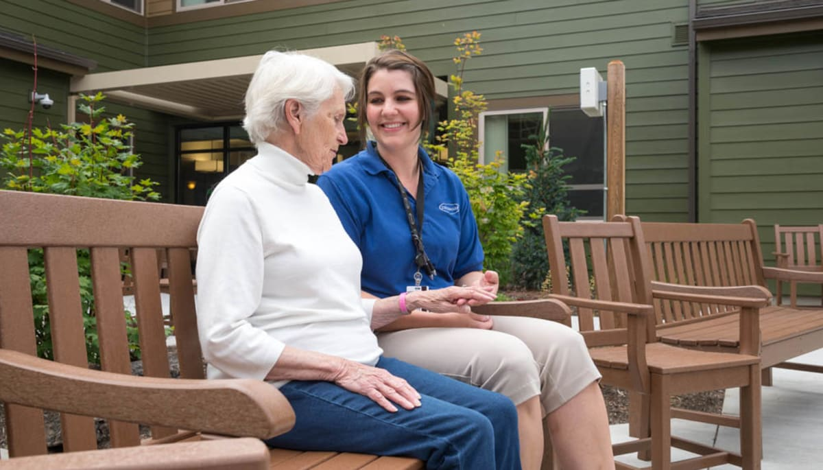 A resident and caretaker having a conversation outside at Touchmark at Mount Bachelor Village in Bend, Oregon