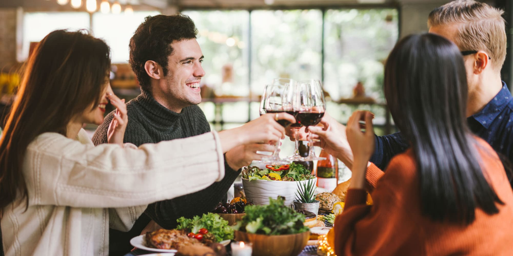 Resident friends enjoying wine and lively conversation before diving into the feast they ordered at their favorite restaurant near L'Estancia in Studio City, California