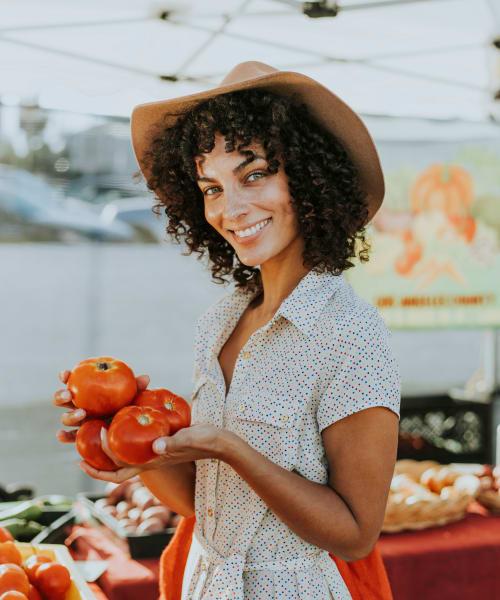 Resident shopping for tomatoes at a farmers market near Hidden Hills Condominium Rentals in Laguna Niguel, California
