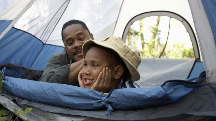 Father smiling at his son while they lay in a tent