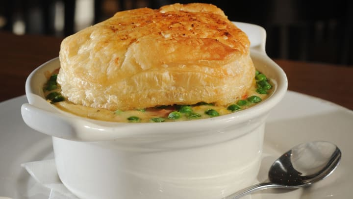 A white ceramic bowl of chicken pot pie with a biscuit on top.