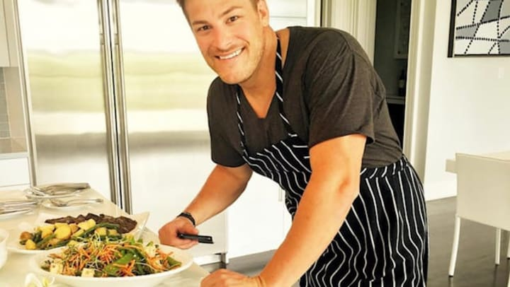 A picture of Paul in a chef apron leaning on a countertop with two vegetable-based meals on white plates.