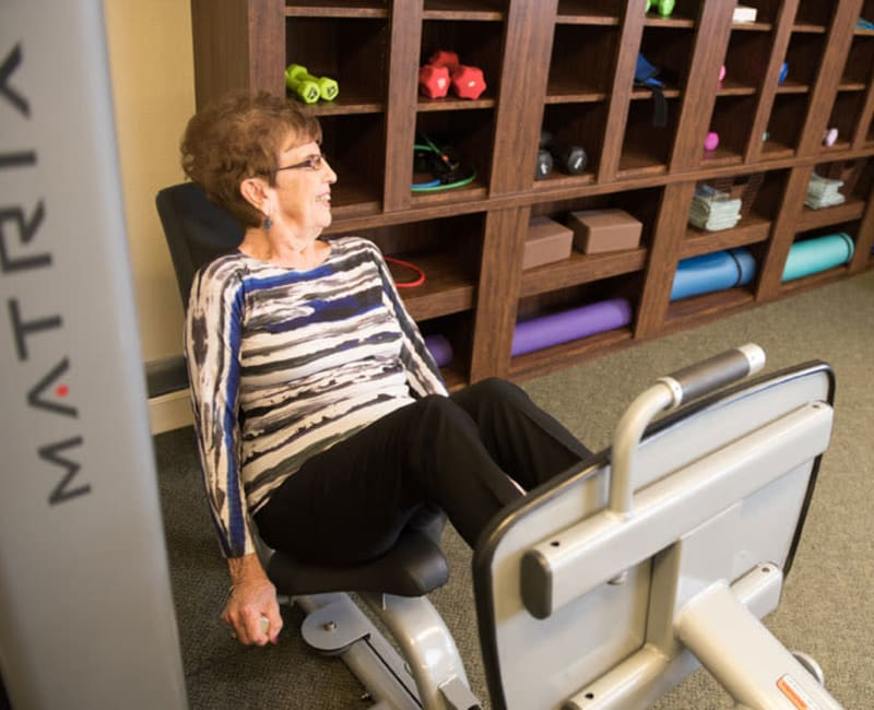 Resident working out with a leg press machine at Deephaven Woods in Deephaven, Minnesota