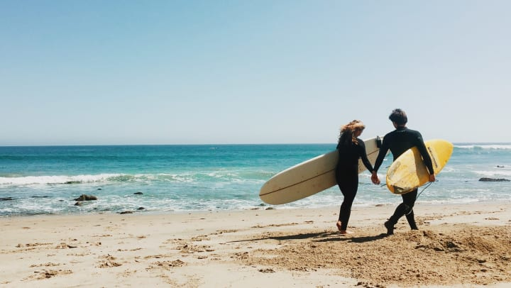 Couple holding hands on the beach, each with a surfboard under an arm.