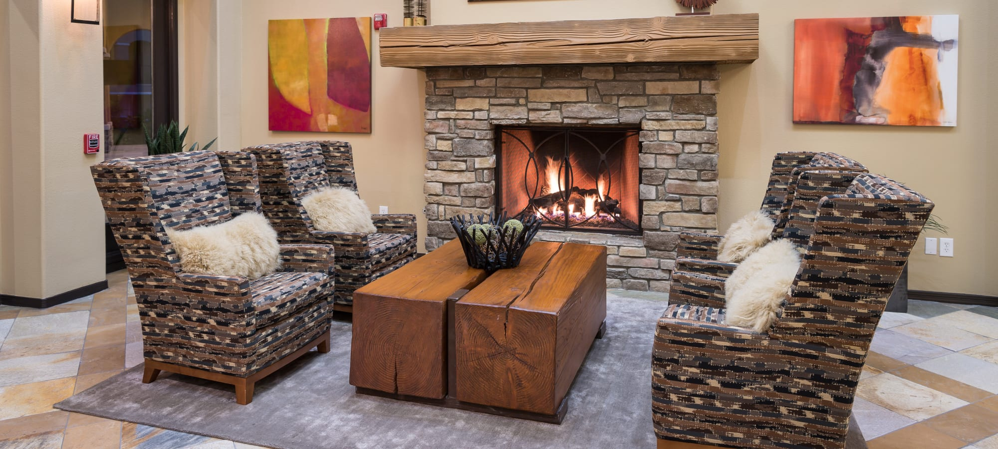 Stone fireplace with comfortable seating nearby in the resident clubhouse at Stone Oaks in Chandler, Arizona