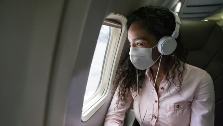 Young woman wearing a mask and headphones sitting in an airplane and looking out the window