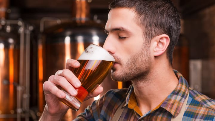 Man drinking a glass of beer.
