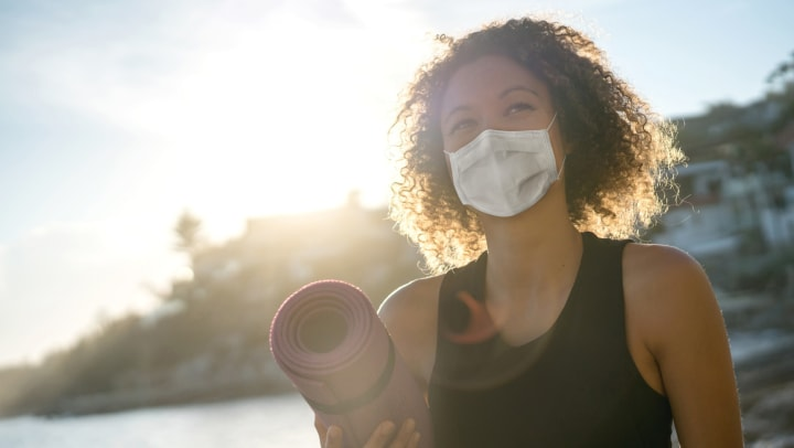 Woman wearing a mask and carrying a yoga mat near Elevation Chandler in Chandler, Arizona