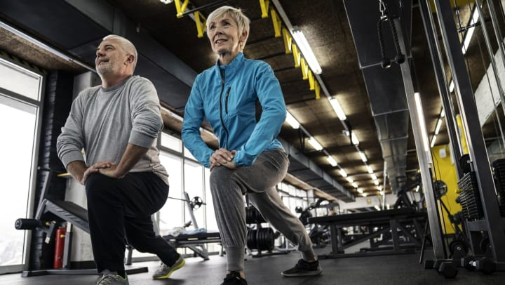 Senior man and woman exercising in a gym.