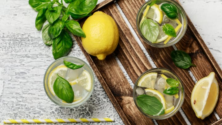 Lemon and mint drinks in glass jars on a wooden tray.
