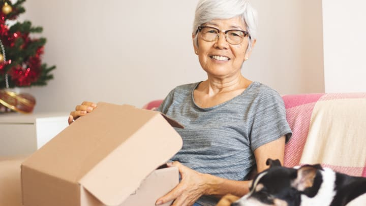 Senior woman sitting on a couch next to a sleeping dog, opening a box, with a Christmas tree in the background.