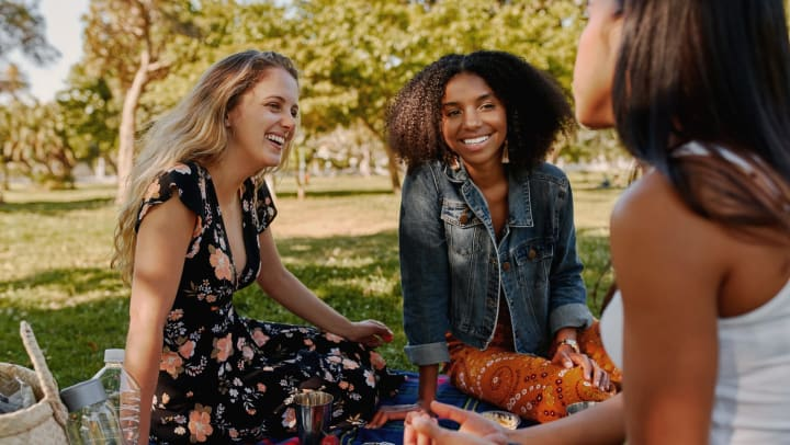 Girls outdoors smiling on a picnic blanket with a container of fruit.