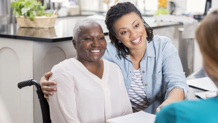 Senior woman in a wheelchair and younger woman smiling and looking toward person in foreground.