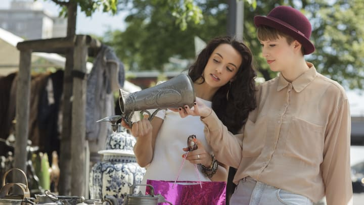 Two women outside holding an antique and looking at it.
