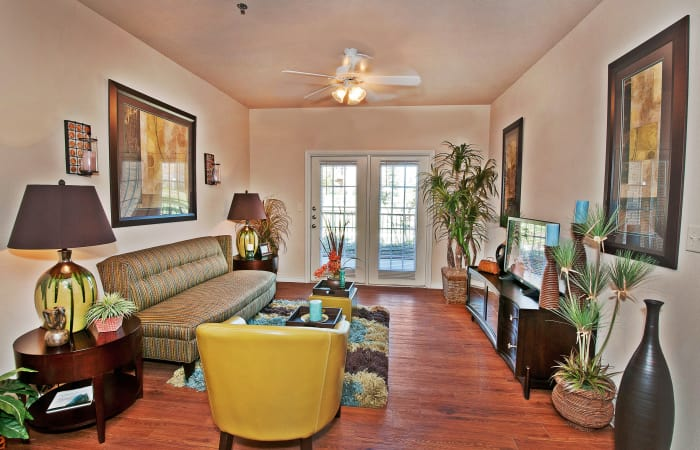 Hardwood floors and ceiling fan in model home's living room at Trails at Buda Ranch in Buda, Texas