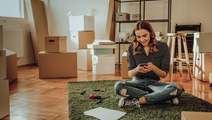 Woman sitting on a carpet on the floor surrounded by moving boxes and other possessions at {{location_name}} in {{location_city}}, {{location_state_name}}