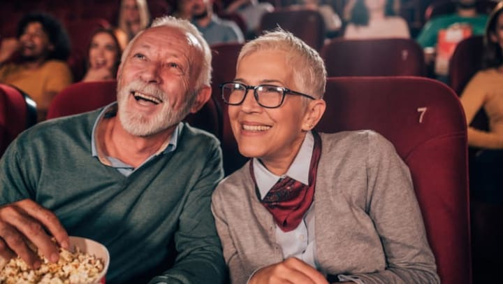 A smiling older couple eating popcorn in a movie theater near {{location_name}} in {{location_city}}, {{location_state_name}}
