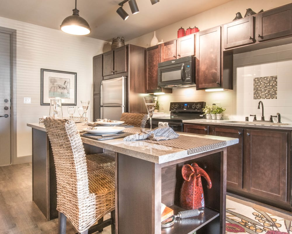 Open-concept gourmet kitchen with an island granite countertops in a model home at Union At Carrollton Square in Carrollton, Texas