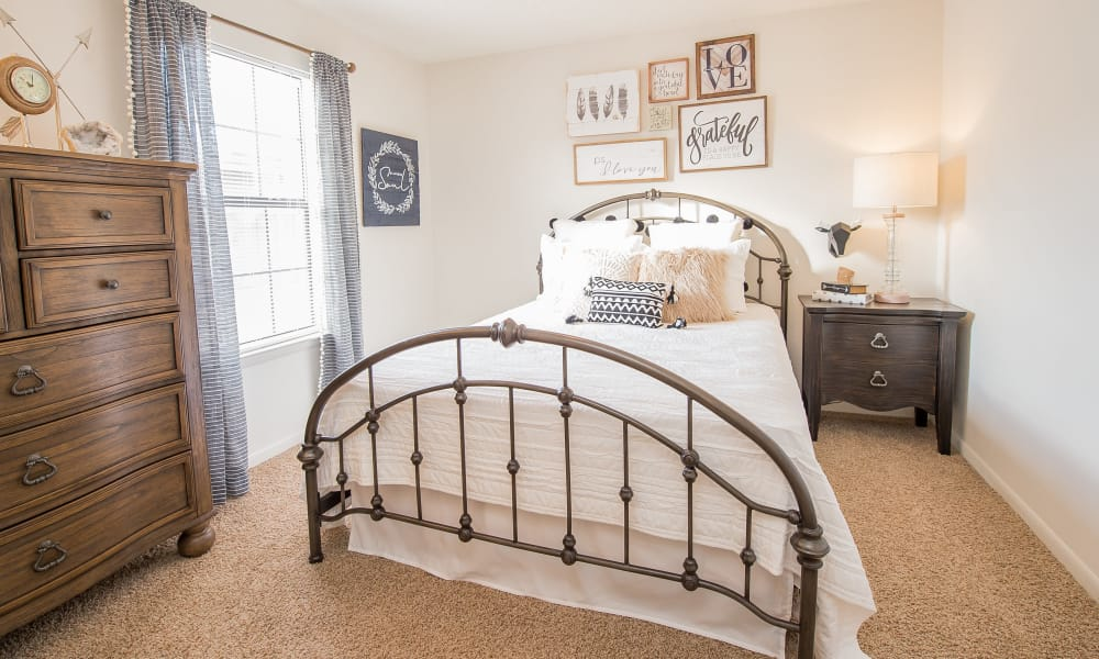 Well-lit bedroom with drapes on the window in model home at Waters Edge in Oklahoma City, Oklahoma