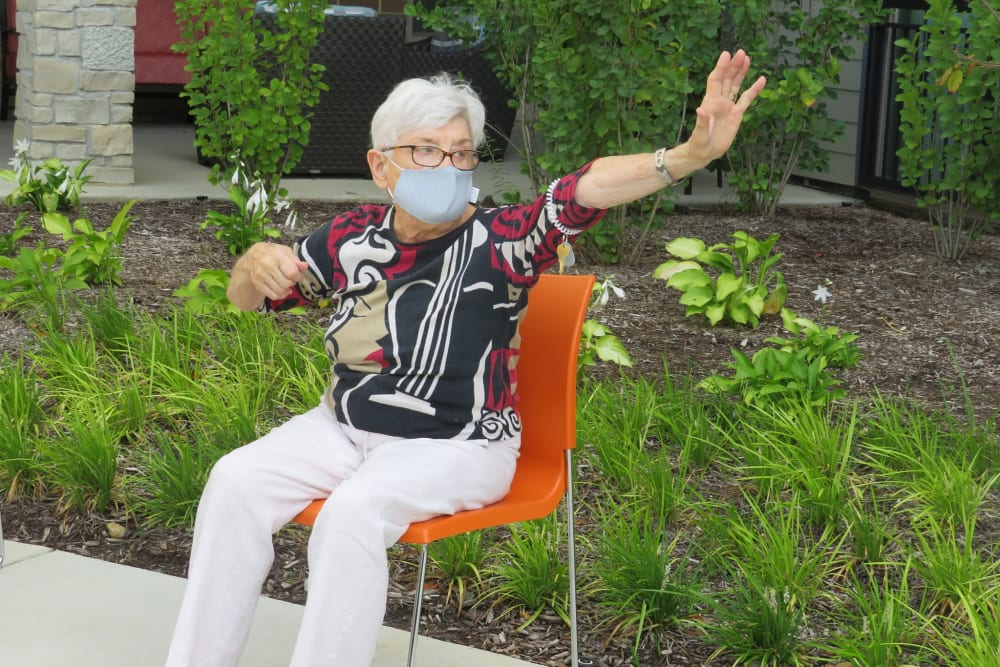 Resident sitting on an orange chair waving to somebody at Aspired Living of La Grange in La Grange, Illinois