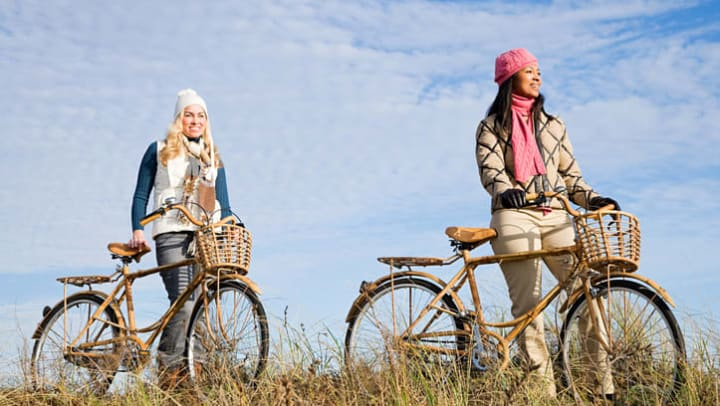 Two women with bikes on a beach shore near {{location_name}}.