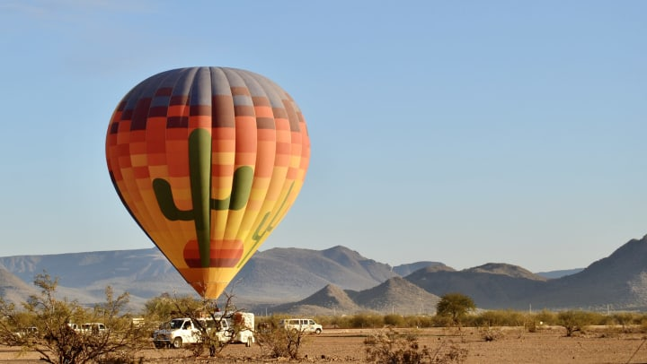 A hot air balloon with giant cactuses painted on it in the middle of a desert.