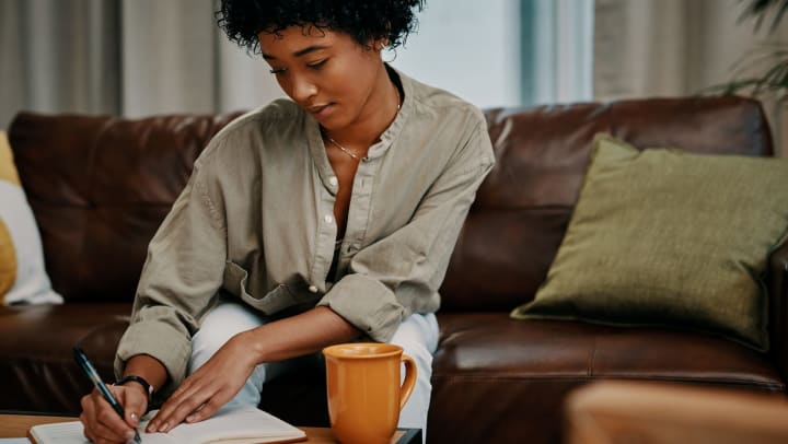 Woman sitting on the couch and writing in a journal with a mug sitting on the table.
