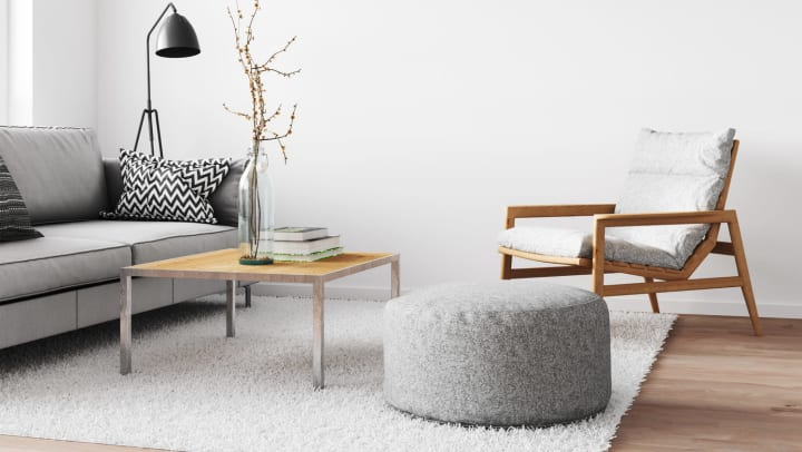 An interior with a grey couch and wood furniture sitting on a white rug.