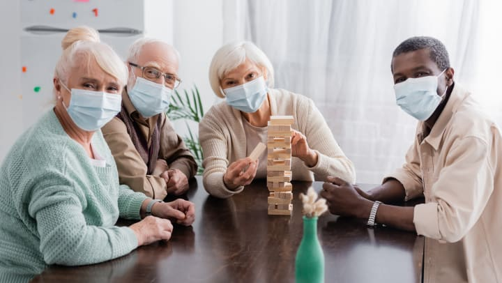 Four residents wearing mask at a table together playing Jenga