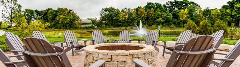 Beautiful waterfront fire pit surrounded by comfortable lawn chairs at The Oaks Of Vernon Hills's lobby in Vernon Hills, Illinois
