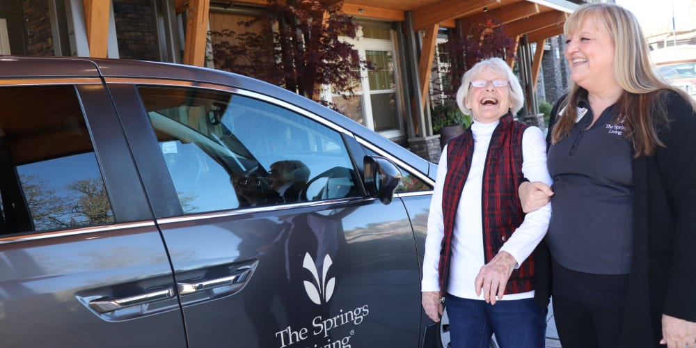 Resident with caregiver next to company vehicle at The Springs at Greer Gardens in Eugene, Oregon.